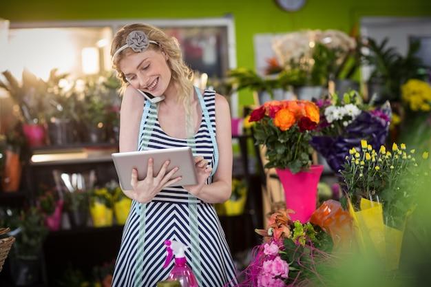 Żeńska kwiaciarnia opowiada na telefonie komórkowym i używa cyfrową pastylkę