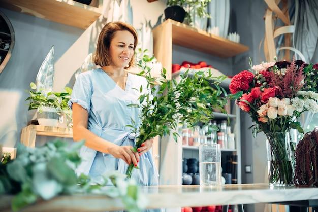 Żeńska kwiaciarnia posiada świeże kwiaty w kwiaciarni. florystyka, tworzenie bukietów