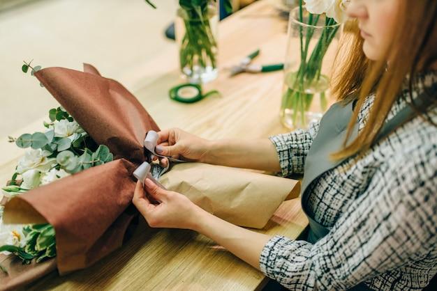 Żeńska kwiaciarnia przyczepia kokardę do kompozycji świeżych kwiatów. biznes kwiatowy, proces przygotowania bukietu, materiały i narzędzia do dekoracji na stole