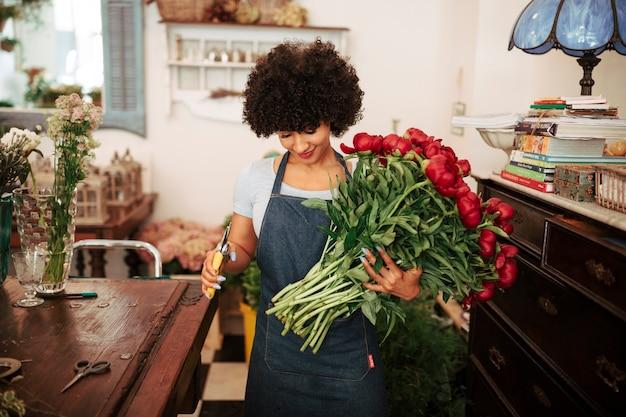 Żeńska kwiaciarnia trzyma wiązkę czerwoni kwiaty