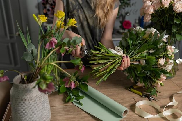 Żeńska kwiaciarnia tworzy pięknego bukiet w kwiatu sklepie, zamyka up