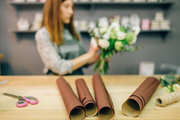 Żeńska kwiaciarnia udekorować bukiet kwiatów. biznes kwiatowy, proces przygotowania kompozycji, materiały do dekoracji stołu