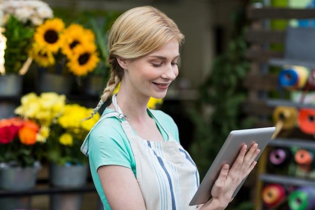 Żeńska kwiaciarnia używa cyfrową pastylkę w kwiaciarnia sklepie