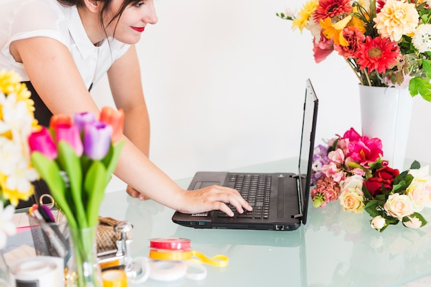 Żeńska kwiaciarnia używa laptop na biurku