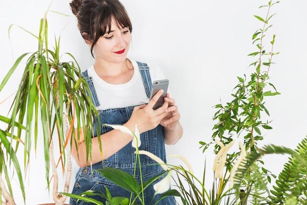 Żeńska kwiaciarnia używa telefon komórkowego blisko zasadza
