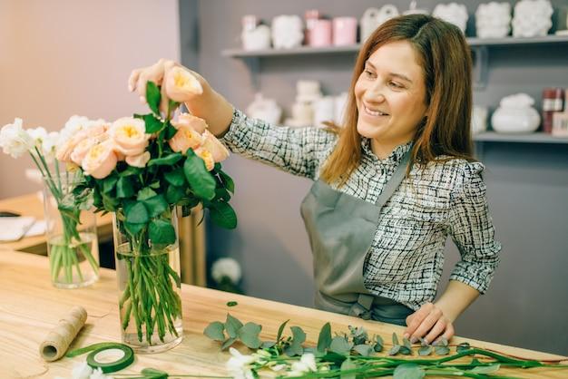 Żeńska Kwiaciarnia W Fartuch Stawia świeże Róże W Wazonie W Kwiaciarni, Kwiatowy Pomysł Na Biznes Premium Zdjęcia