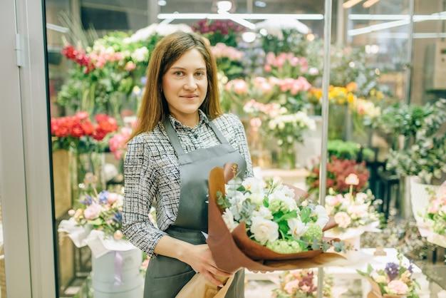 Żeńska kwiaciarnia w fartuch ze świeżym bukietem w kwiaciarni, kwiatowy koncepcja biznesowa