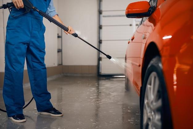 Żeńska myjka w mundurze czyści auto z pistoletem wysokociśnieniowym w rękach