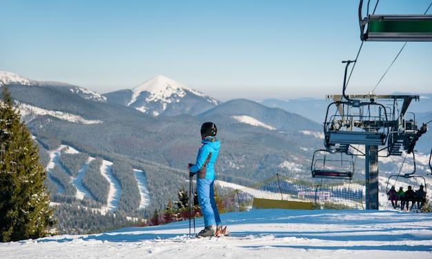 Żeńska narciarka odpoczywa po narciarstwa patrzeje daleko od cieszący się oszałamiająco zim gór widok przy ośrodkiem narciarskim