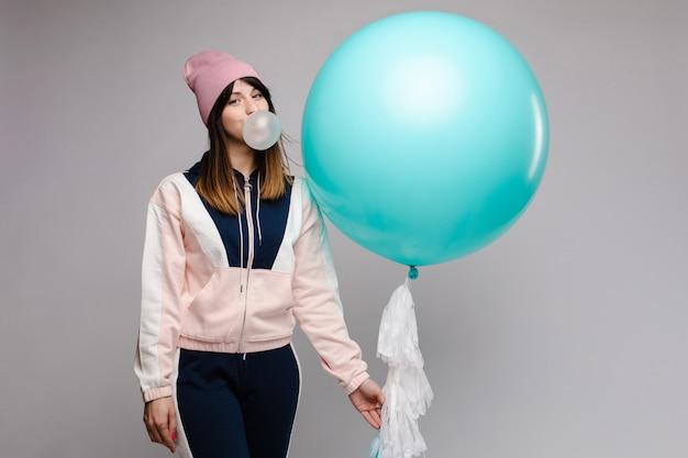 Żeńska nastolatka guma do żucia i utrzymanie dużego niebieskiego balonu