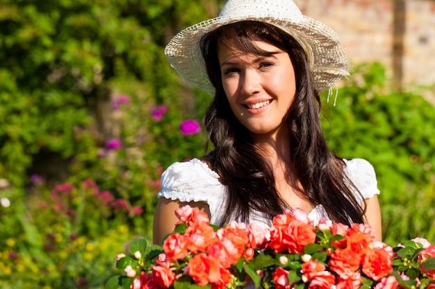 Żeńska ogrodniczka z słomianym kapeluszem pozuje z kwiatami