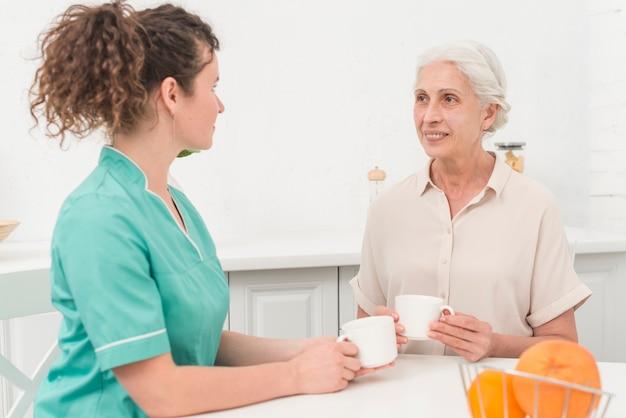 Żeńska pielęgniarka pije kawę z starszą kobietą