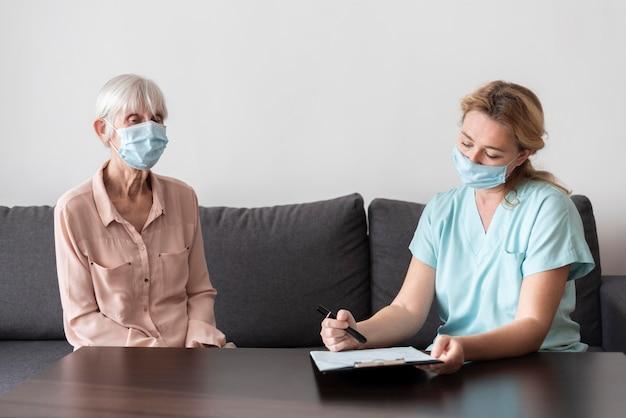 Żeńska pielęgniarka po kontroli ze starszą kobietą w domu opieki
