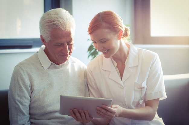 Żeńska pielęgniarka pokazuje raport medycznego starszy mężczyzna na cyfrowej pastylce