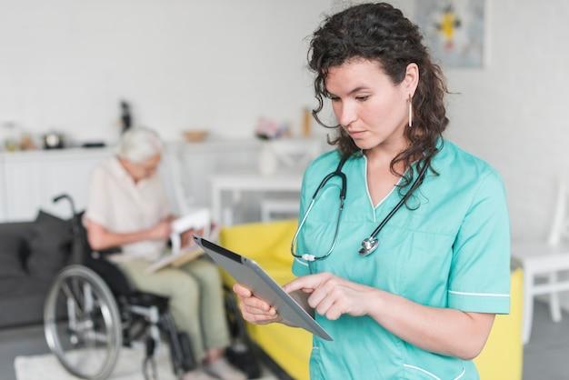 Żeńska pielęgniarka używa cyfrową pastylki pozycję przed starszym kobiety obsiadaniem na wózku inwalidzkim