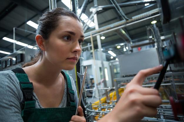 Żeńska pracownik fabryczny działająca maszyna