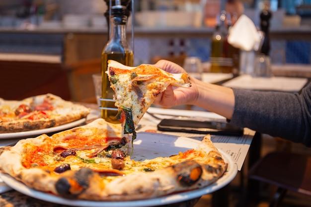 Żeńska ręka bierze plasterki smakowita pizza od talerza w restauraci.