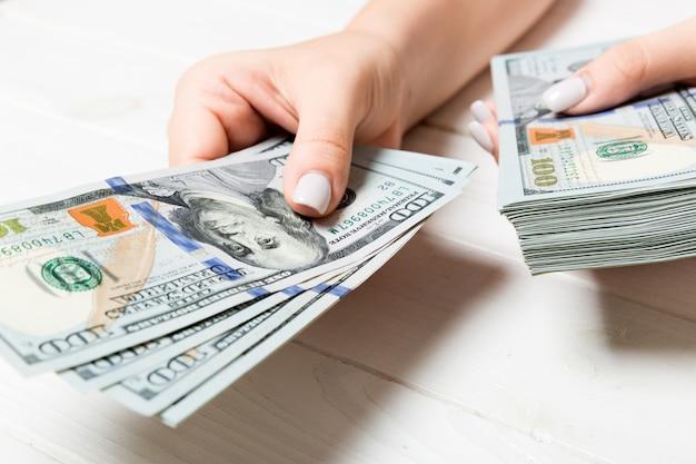Żeńska ręka daje sto dolarowym banknotom na drewnianym stole