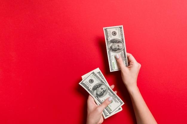 Żeńska ręka daje sto dolarowym banknotom