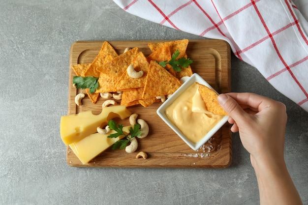 Żeńska ręka dipuje chip w sosie serowym na tle przekąsek, widok z góry