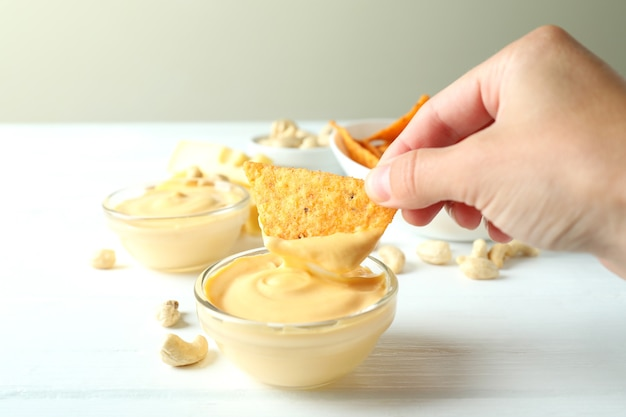 Żeńska ręka dipuje chipsy w sosie serowym, z bliska