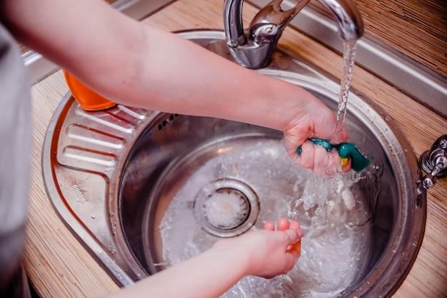 Żeńska ręka domycie naczynie gąbka z dishwashing mydłem. koncepcja czyszczenia domu.