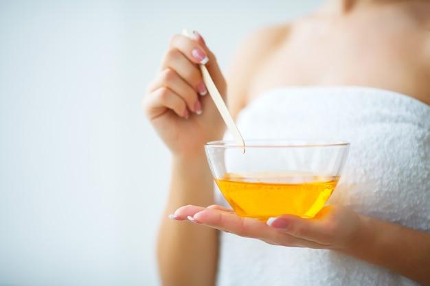 Żeńska ręka i pomarańczowy wosk parafinowy w misce.