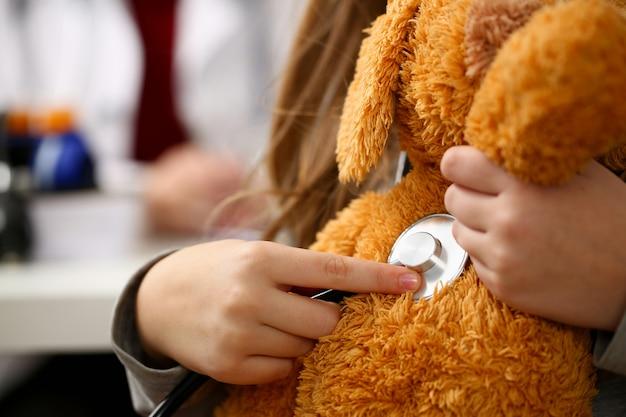 Żeńska ręka mała dziewczynka chwyta stetoskop słucha
