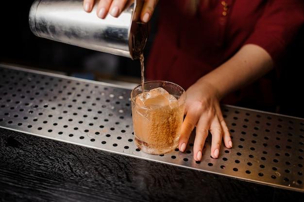 Żeńska ręka nalewa świeżego napój od shaker do szkła