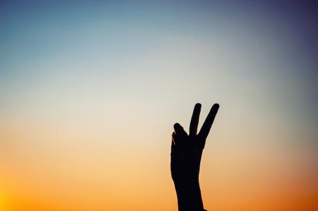 Żeńska ręka pokazuje sylwetka znaka zwycięstwo przy zmierzchem lub, kopia przestrzeń