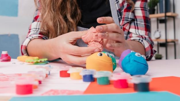 Żeńska ręka robi kreskówka twarzom używać kolorową glinę