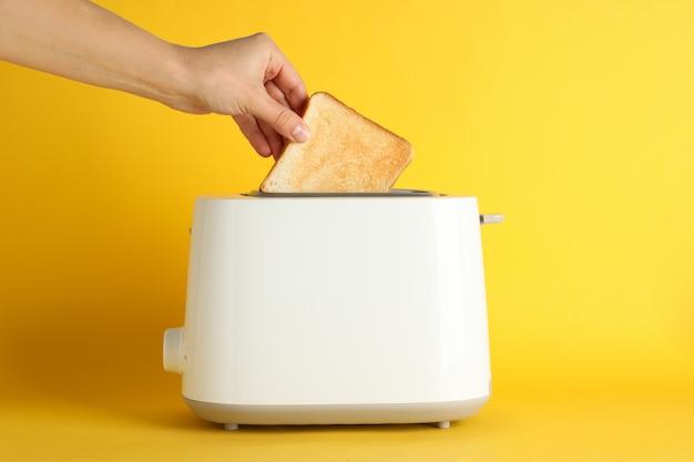 Żeńska ręka stawia chleb w opiekaczu na żółtym tle, przestrzeń dla teksta