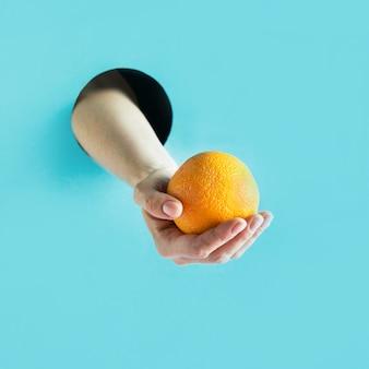 Żeńska ręka trzyma dojrzałą pomarańcze w papierowej dziurze.
