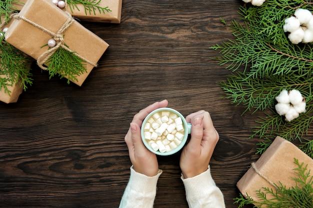 Żeńska ręka trzyma filiżankę czekolady z marshmallow i prezenta pudełkami na ciemnym drewnianym, odgórnym widoku ,.