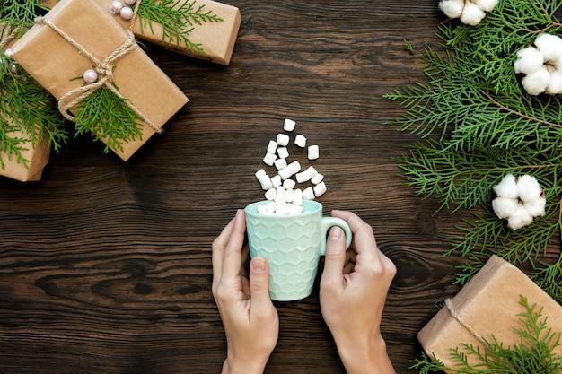 Żeńska ręka trzyma filiżankę czekolady z marshmallow i prezenta pudełkami na ciemnym drewnie