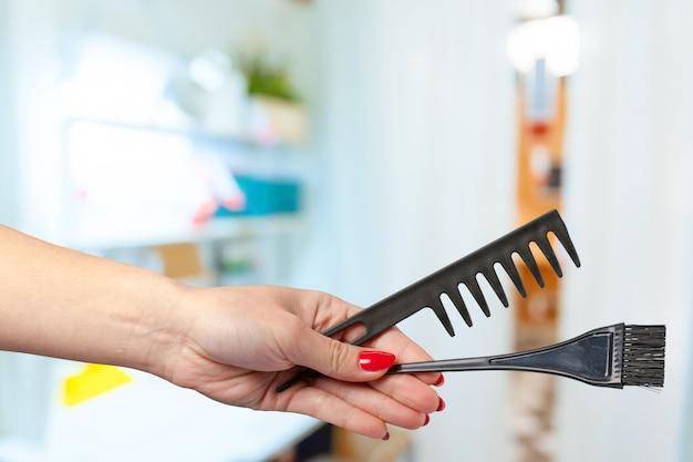 Żeńska ręka trzyma fryzjer męski grzebień w kosmetycznym sklepie
