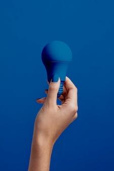 Żeńska ręka trzyma klasyczną błękitną żarówkę