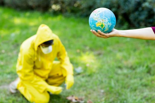 Żeńska ręka trzyma kulę ziemską. za mężczyzną w żółtym garniturze podpala się suche liście.