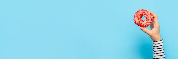 Żeńska ręka trzyma pączek na błękitnym tle. koncepcja cukierni, cukierni, kawiarni.
