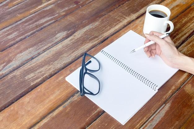 Żeńska ręka trzyma pióro. stół z notatnikami. przerwa na kawę. czarne szkło.