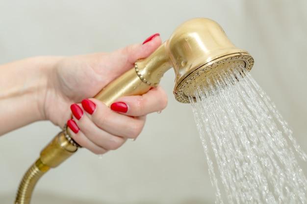 Żeńska ręka trzyma prysznic głowę