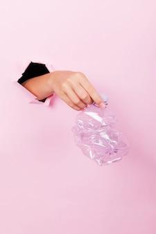 Żeńska ręka trzyma przez dziury pustą zmiętą plastikową butelkę na różowym tle, nie ma plastiku i zero koncepcji odpadów