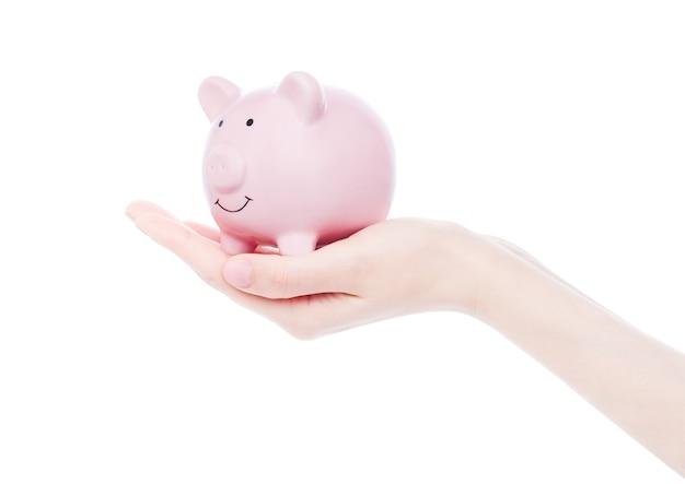 Żeńska ręka trzyma różowego prosiątko banka na białym tle