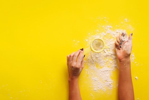 Żeńska ręka trzyma sito mąkę na żółtym tle.