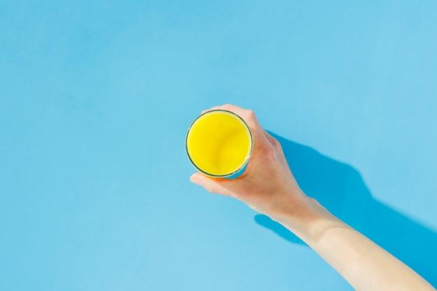 Żeńska ręka trzyma szkło sok pomarańczowy na błękitnym tle. pojęcie witamin, zwrotnik, lato, napój pragnienia. minimalizm. naturalne światło. leżał płasko, widok z góry.