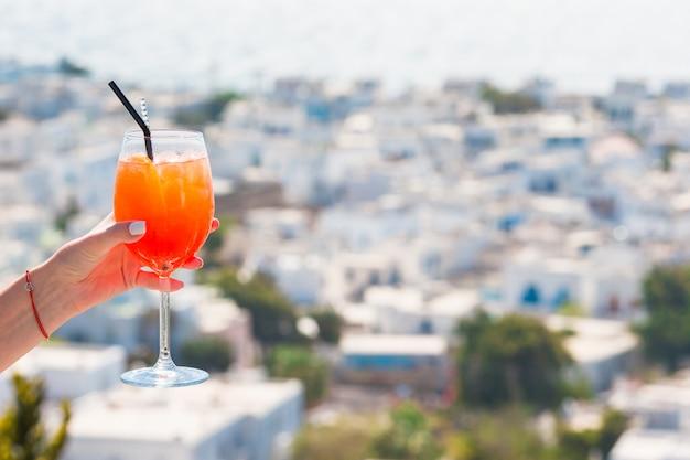 Żeńska ręka trzyma szkło z alkoholu napoju spritz aperol tłem w pięknym starym mykonos w grecja