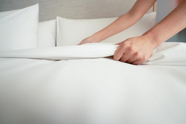 Żeńska ręka ustawia białą prześcieradło w hotelowym pokoju