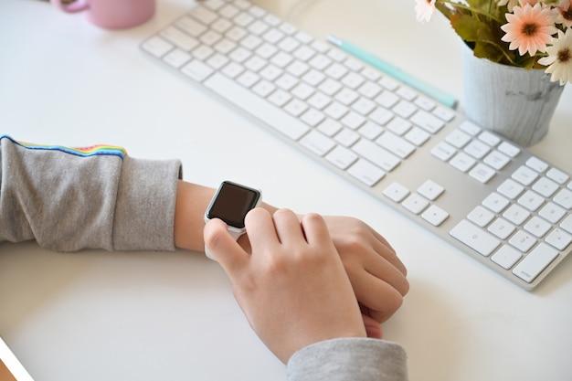 Żeńska ręka używać mądrze zegarek na miejscu pracy.