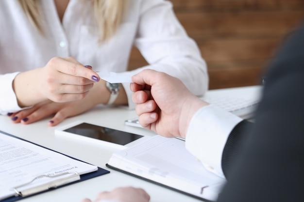 Żeńska ręka w kostiumu daje pustej wizytówce męski gościa zbliżenie. przedstawiciele białych kołnierzyków dyrektorzy giełdowi lub dyrektorzy firmy przedstawiający na konferencji doradcę ds. sprzedaży produktu