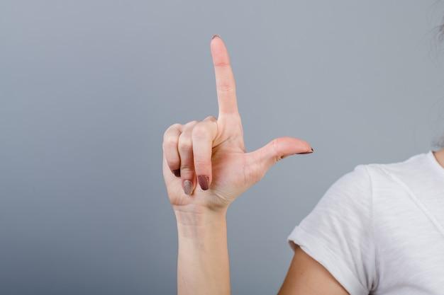 Żeńska ręka w pięści pokazuje dwa palca odizolowywającego nad popielatym